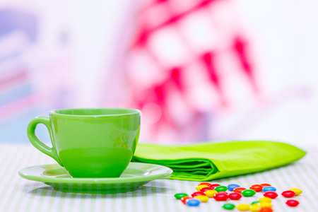 Tea cup and candy dragees on the table photo