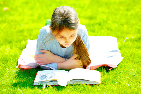 girl reading a book on the grass photo