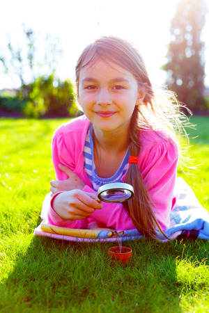 girl looking through a magnifying glass on the grass photo