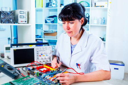 technical service: woman repairs computer board