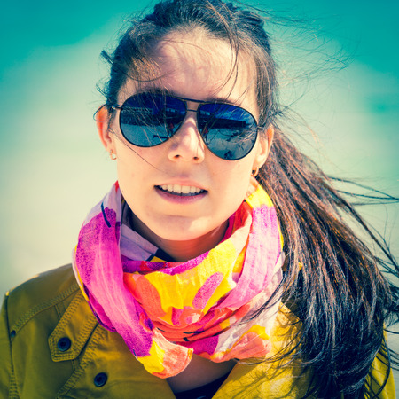 teen girl face: girl in sunglasses with a scarf on a neck