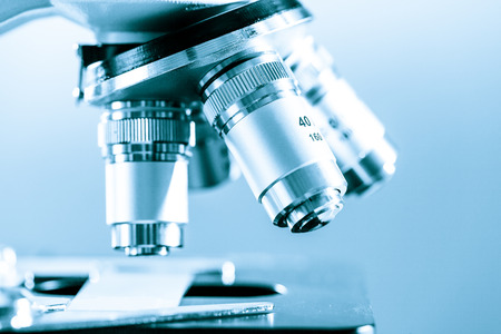 medical study: Scientific microscope lens on blue background, A microscope is an instrument used to see too small objects Stock Photo