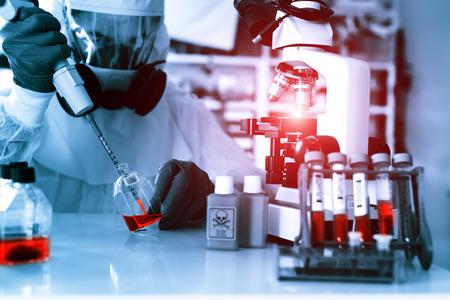 microbiologia: El examen de laboratorio de Ebola. Científico toma pipeta sangre y estudios con el microscopio en muestras biológicas.