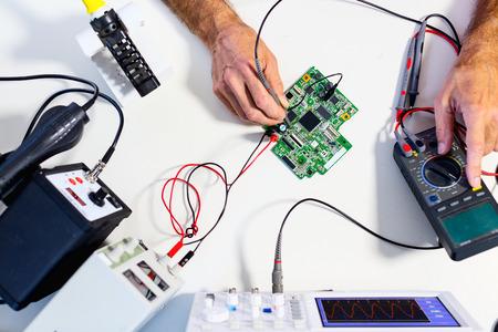 Développement de dispositifs électroniques dans le laboratoire d'électronique moderne, sur une table, microprocesseur oscilloscope et multimètre