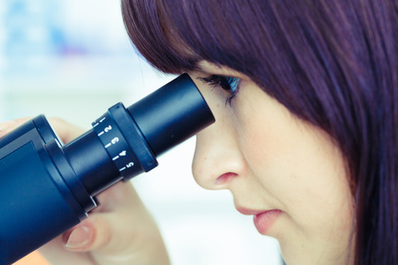 student girl looking in a microscope, science laboratory concept photo
