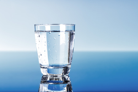 reflection  water: Drinking water in glass on blue Stock Photo