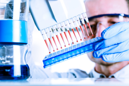 sample tray: Scientist uses multipipette during DNA research Stock Photo