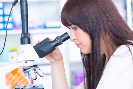 cancer research: student girl looking in a microscope, science laboratory concept