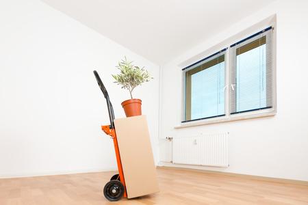 carretilla de mano: cajas de cartón en un apartamento vacío. mudarse a un apartamento nuevo carro de mano Foto de archivo