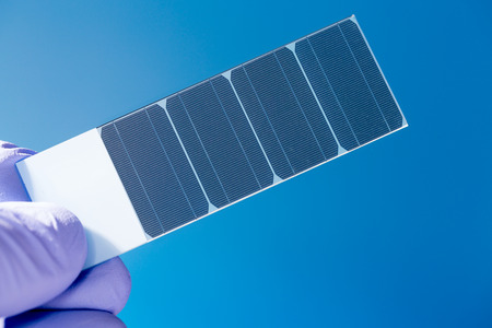 silicon crystal with photovoltaic cells in the hand of the scientist