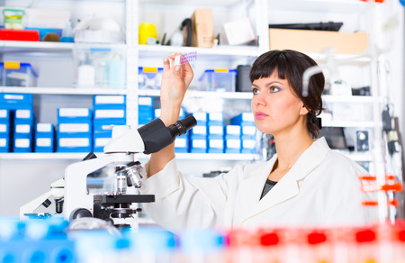 biopsy: woman in a laboratory microscope with microscope slide in hand