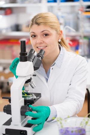 microbiologia: Científico joven mujer utilizando un microscopio en un laboratorio de ciencias