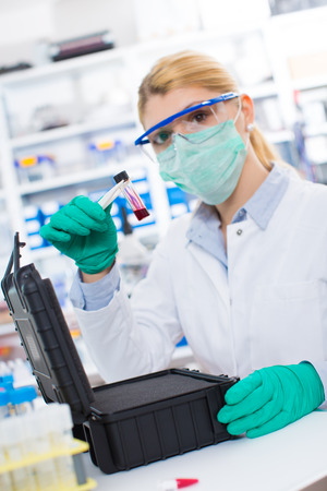 hazardous: bottle of hazardous substances  ebola virus  on the hands of a woman scientist Stock Photo