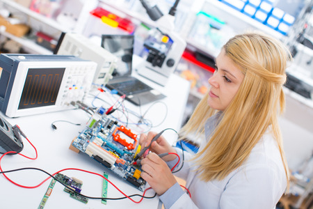 computer services: girl with a tester and a printed circuit board