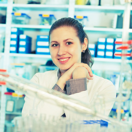 Young  scientist woman in a chemistry lab looking at the camera and smiling photo