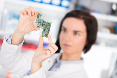 debugging: girl student studying electronic device with a microprocessor
