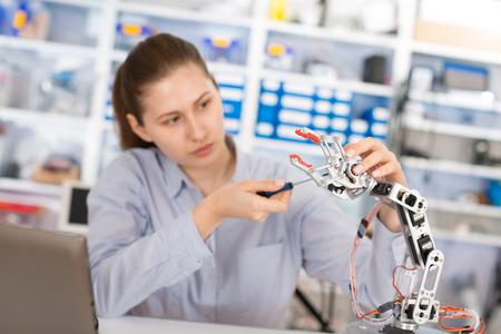 colegiala ajusta el modelo de brazo robot, chica en un laboratorio de robótica