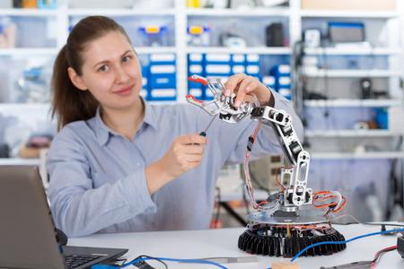 schoolgirl adjusts the robot arm model, girl in a robotics laboratory Standard-Bild