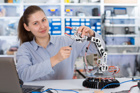 schoolgirl adjusts the robot arm model, girl in a robotics laboratory Stock Photo