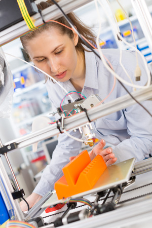 schoolgirl adjusts the robot arm model, girl in a robotics laboratory photo