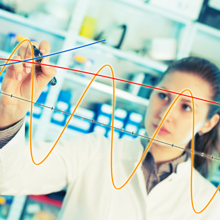 Woman laboratory assistant draws a graph on a glass photo