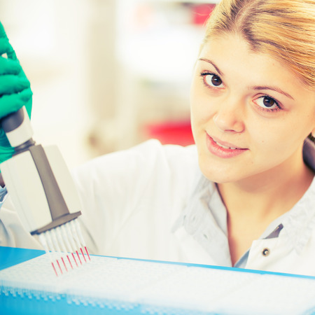 womanl with multi pipette in the laboratory of microbiology photo