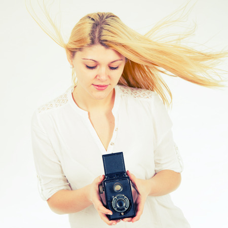 girl on a white background with retro camera photo