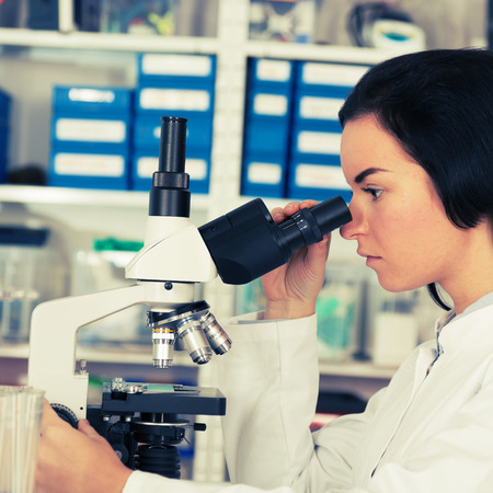 Scientist young woman using a microscope in a science laboratory photo