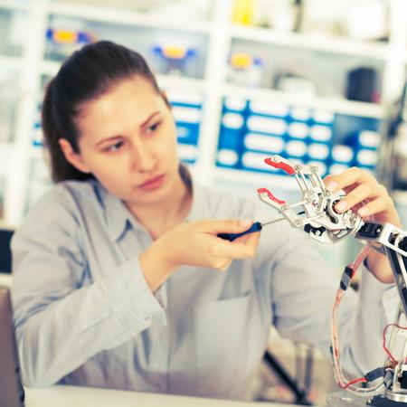 production engineer: schoolgirl adjusts the robot arm model, girl in a robotics laboratory Stock Photo