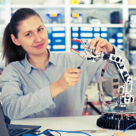 schoolgirl adjusts the robot arm model, girl in a robotics laboratory Stock Photo