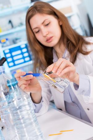 agua: chica en las pruebas de laboratorio del agua bebida. Comprueba el contenido de sal y minerales Foto de archivo