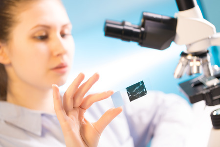 specimen: woman in a laboratory microscope with microscope slide in hand