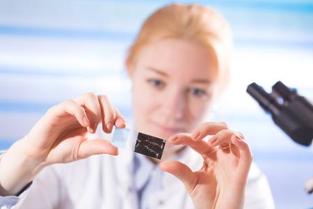 microscope slide: woman in a laboratory microscope with microscope slide in hand