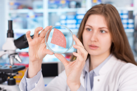 food inspection: girl in the laboratory of food quality tests sausage
