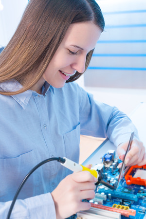 Girl repairing electronic device on the circuit board photo