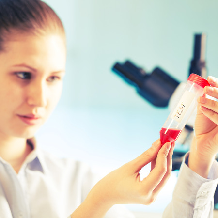 blood test: Young student woman medical  scientific researcher  doctor looking at a test tube of liquid in science laboratory, blood test