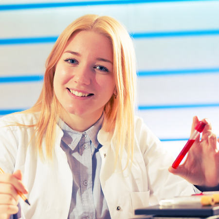 Young student woman medical  scientific researcher  doctor looking at a test tube of liquid in science laboratory, blood test photo