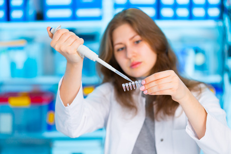 Girl with a pipette in a lab University Hospital photo