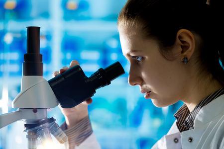 Biopsia: Chica estudiante busca en un microscopio, el concepto de laboratorio de ciencias Foto de archivo