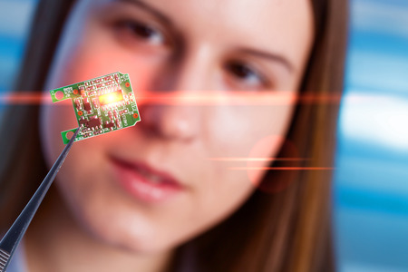 developed: Girl shows new microchip on plate  that can be implanted into a paralyzed patient, developed a microchip muscle simulator Stock Photo