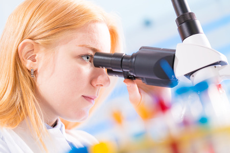 biopsy: student girl looking in a microscope, science laboratory concept