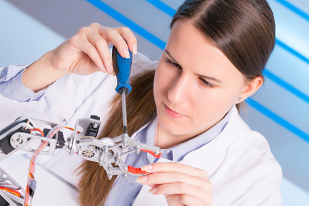 robot girl: schoolgirl adjusts the robot arm model, girl in a robotics laboratory Stock Photo