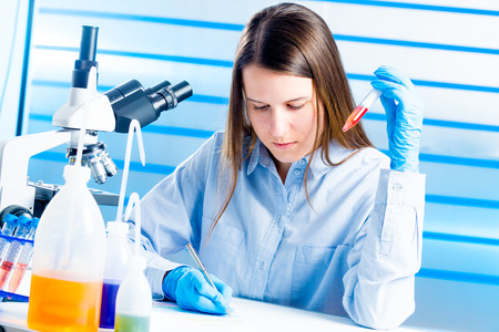 lab technician: Technician with test tube  in a medical lab