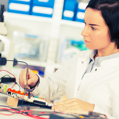 laboratory technician: Woman  with a tester and a printed circuit board