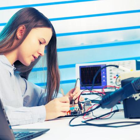 circuitos electricos: Muchacha que repara el dispositivo electr�nico en el circuito