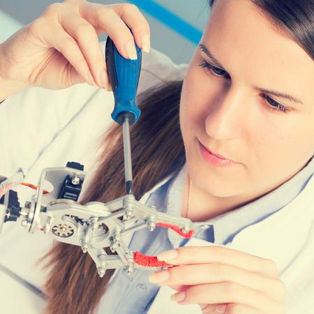 физика: школьница регулирует модель руки робота, девочка в робототехники лаборатории Фото со стока