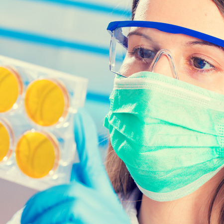 Technician with petri dishes in a medical lab photo