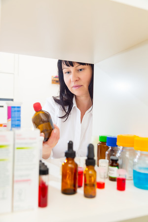 woman takes a bottle of medicine from the pharmacy photo