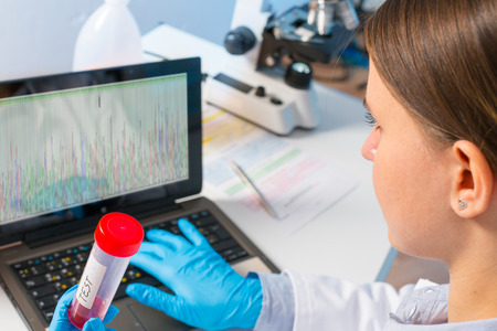 laboratory assistant analyzes of DNA sequence on the computer photo