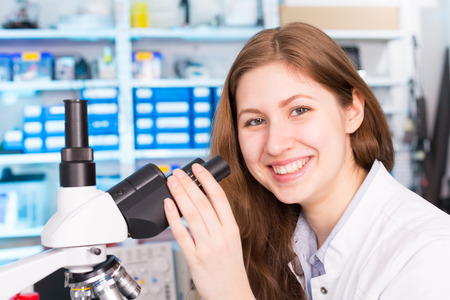 medical test: technician in the laboratory using a microscope, girl smiling